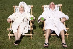 Retired couple in robes with drinks in rope chairs relaxing in the sun.