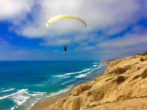 Paraglider soaring high above the Pacific Ocean in San Diego